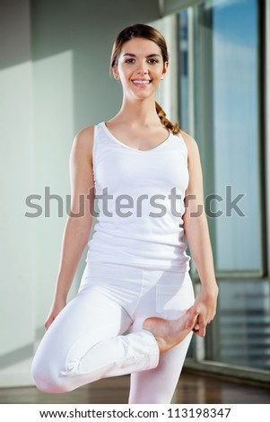 Portrait of a happy young woman practicing yoga at gym - stock photo