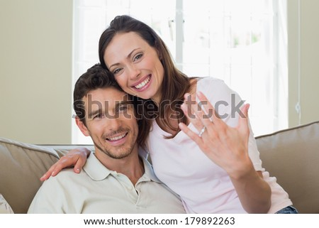 Portrait of a happy young woman showing engagement ring besides man at home - stock photo