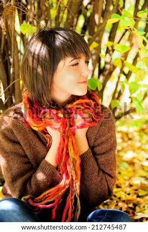 Portrait of a happy young woman sitting in autumn park.  - stock photo