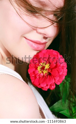 Portrait of a happy young woman smelling the fragrance of a flower - stock photo