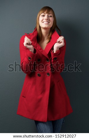 Portrait of a happy young woman smiling in red winter jacket - stock photo