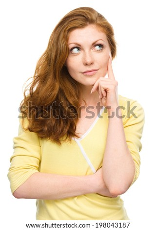 Portrait of a happy young woman thinking about something while touching her cheek with finger, isolated over white - stock photo