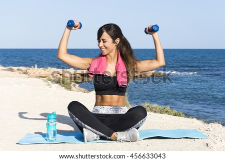 Portrait of a healthy beautiful teenager girl exercising on the beach lifting weights during an exercise and sport routine against an intense blue sky. Sporty healthy lifestyle outdoors. - stock photo