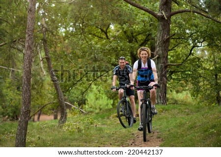 Portrait of a healthy couple enjoying a bike ride in nature - stock photo