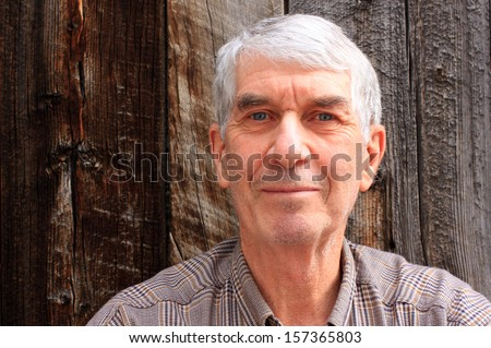 Portrait of a healthy senior man with a barn wood background. - stock photo