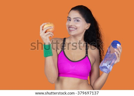 Portrait of a healthy woman holding apple and bottle of water while smiling at camera - stock photo