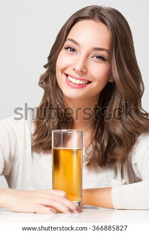 Portrait of a healthy young brunette beauty with glass of apple juice. - stock photo