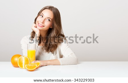 Portrait of a healthy young brunette beauty with glass of orange juice and fruit. - stock photo