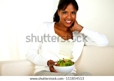 Portrait of a healthy young woman sitting on a sofa while holding a vegetable saladl and looking at you. - stock photo