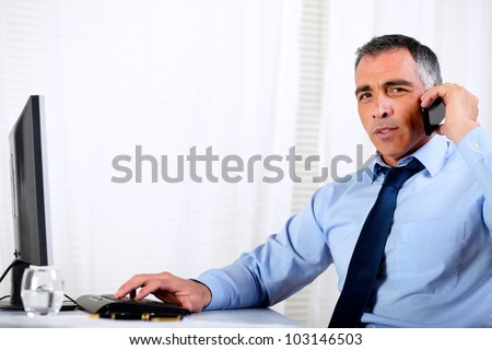 Portrait of a hispanic professional man conversing on mobile at the company office - stock photo
