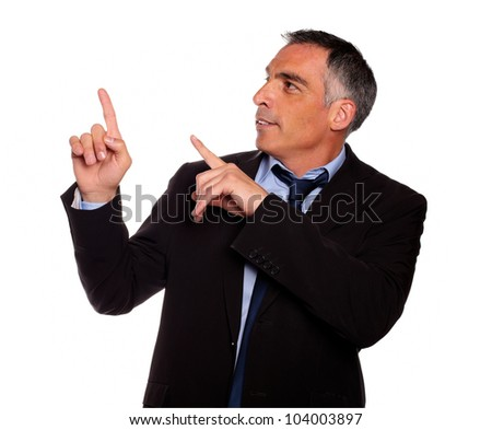 Portrait of a hispanic senior entrepreneur pointing up on black suit against white background - stock photo