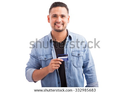 Portrait of a Hispanic young man dressed casually and holding his favorite credit card against a white background - stock photo
