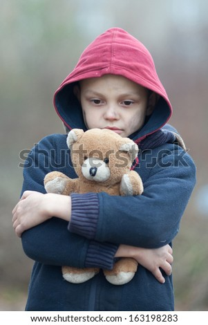 portrait of a homeless boy with bear - stock photo