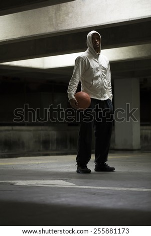 Portrait of a hooded basketball player holding a ball in an inner city urban environment - stock photo