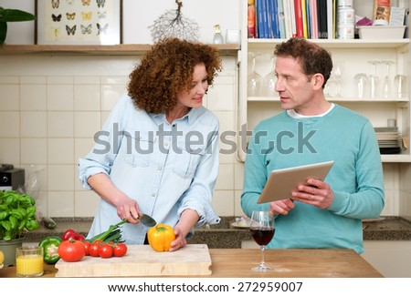 Portrait of a husband and wife reading recipe from tablet - stock photo