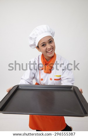 Portrait of a Indian woman with chef uniform holding an empty tray - stock photo