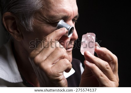 portrait of a jeweler during the evaluation of jewels - stock photo