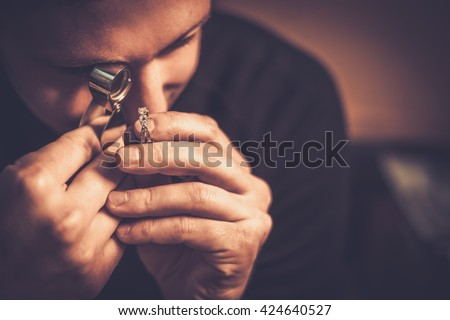 Portrait of a jeweler during the evaluation of jewels. - stock photo