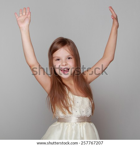 Portrait of a joyful emotional little girl with long hair jumping and dancing on a gray background - stock photo