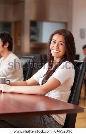 Portrait of a joyful woman having a cup of tea in a cafe - stock photo