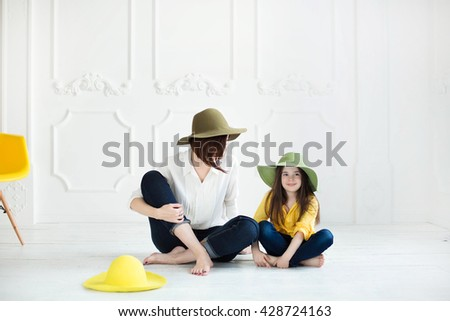 Portrait of a joyful young mother with a cute cheerful daughter wearing same straw hats and playing at home, laughing and having fun, portrait of a happy family enjoying life - stock photo