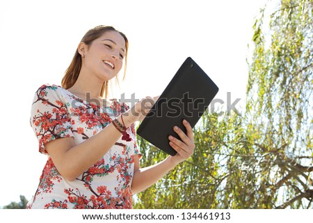 Portrait of a joyful young woman in a park using a digital tablet pad during a sunny day with a blue sky. - stock photo