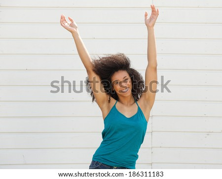 Portrait of a joyful young woman with arms up in the air - stock photo