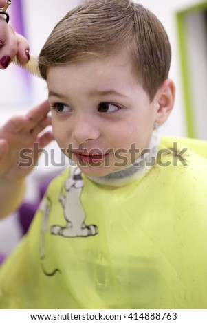 Portrait of a kid at the barbershop - stock photo