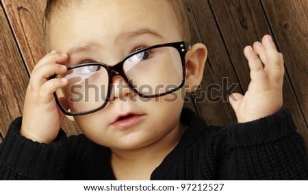 portrait of a kid wearing glasses against a wooden background - stock photo