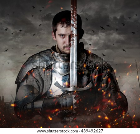 Portrait of a knight with sword on batllefield. - stock photo
