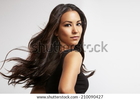 portrait of a latin woman with blowing windy hair - stock photo