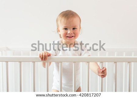 Portrait of a laughing baby standing in a crib and looking at the camera - stock photo