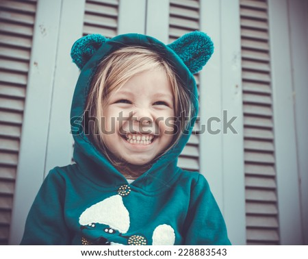 Portrait of a laughing little girl wearing green hooded smock - stock photo