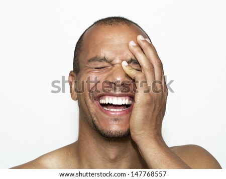 Portrait of a Laughing Man with his hand on his face - stock photo