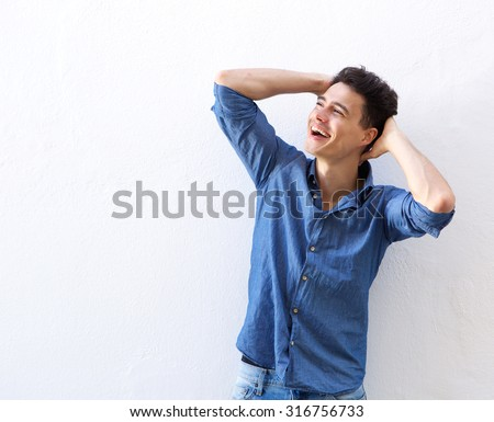 Portrait of a laughing young man with hands in hair against white background - stock photo