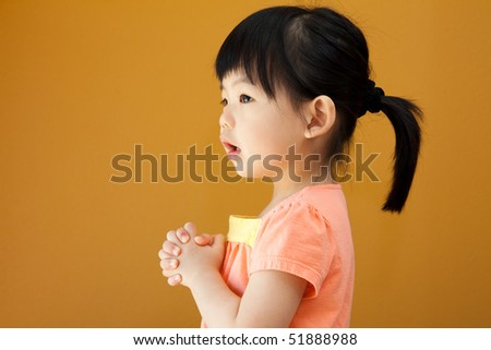 Portrait of a little Asian baby child girl is praying - stock photo