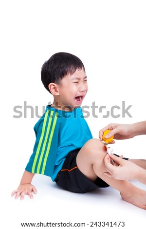 Portrait of a little asian boy (thai) crying, his mother clean and provides first-aid at wound his leg, Isolated on white background - stock photo