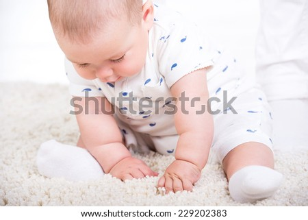 Portrait of a little baby boy is sitting on the floor. - stock photo