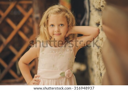Portrait of a little blond girl smiles at the camera near the stone wall. cute little girl smiling in a park close-up. - stock photo