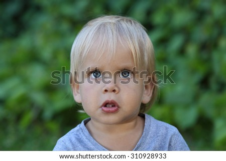 Portrait of a little boy. Emotions of the child. The child is looking up - stock photo