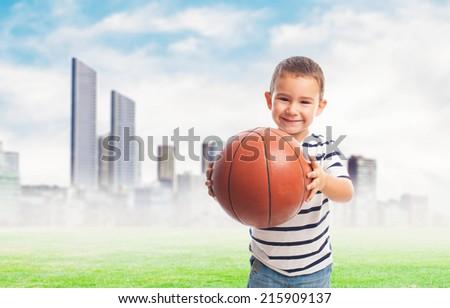 portrait of a little boy holding a basket ball - stock photo