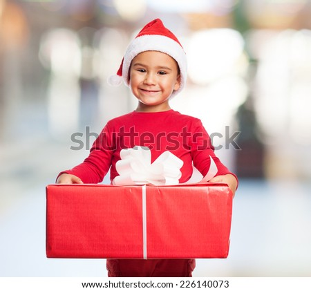 portrait of a little boy holding a big gift - stock photo