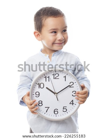 portrait of a little boy holding a clock - stock photo