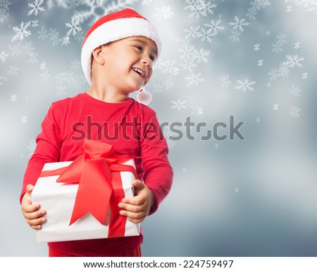 portrait of a little boy holding a white gift - stock photo