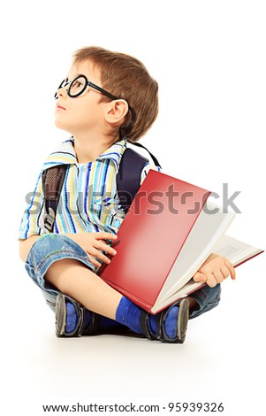 Portrait of a little boy in spectacles reading a book. Isolated over white background. - stock photo