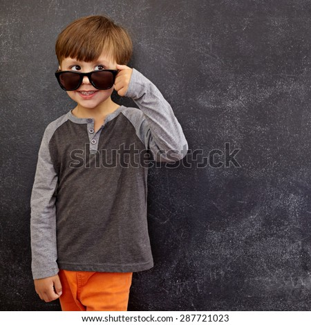 Portrait of a little boy in sunglasses looking at away at copy space. Cool boy peering over his sunglasses against blackboard. - stock photo