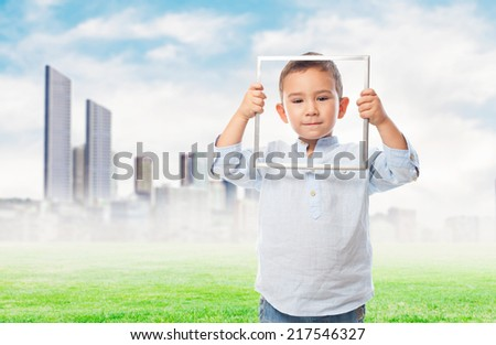 portrait of a little boy looking through an empty frame - stock photo