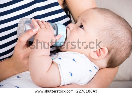 Portrait of a little boy, mother is feeding him. Close-up. - stock photo
