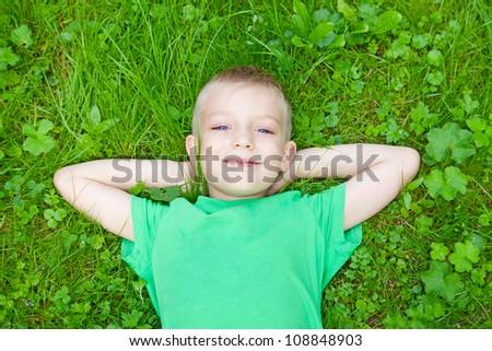 portrait of a little boy on meadow - stock photo