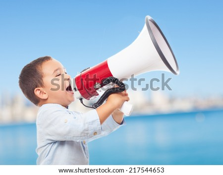 portrait of a little boy shouting with the megaphone - stock photo